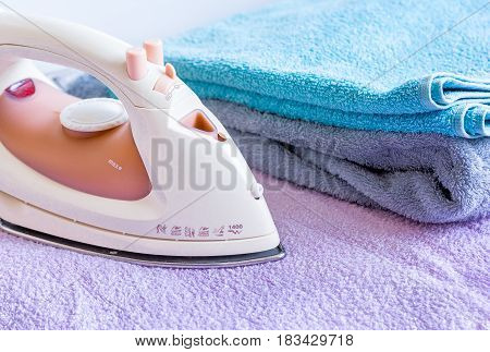 colorful bath towels stack with iron in laundry on fabric background