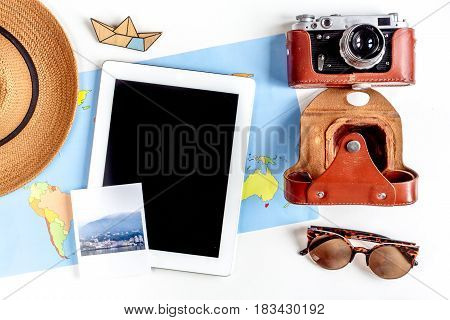 vacation concept with traveller outfit map and tablet on white desk background top view