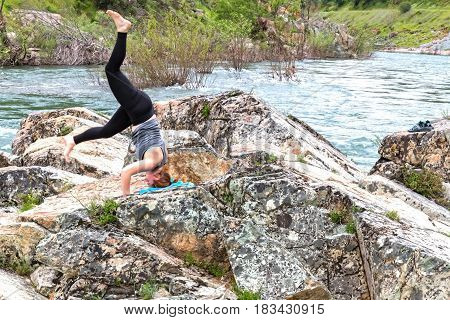 Young Girl Trying to do a Handstand on Rocks Near Fast River