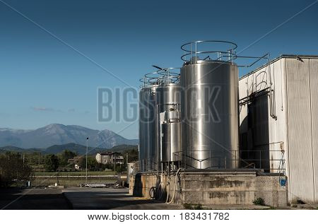 Industrial silos storage structures external view in mountainous location blue cloudy sky
