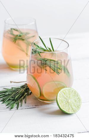 healthy morning with fresh drink, sliced lime and rosemary on white table background