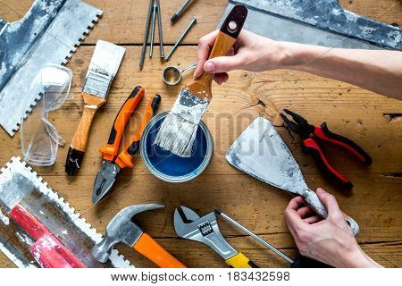 building decoration instruments with paint, brush, palette-knife in builder work on wooden background top view