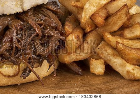 Close up on pulled pork sandwich and french fries.
