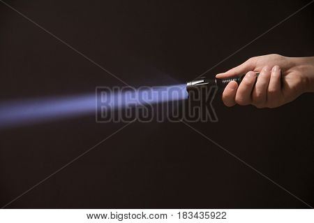 Led Flashlight In The Man's Hand From The Right Side Of The Frame.