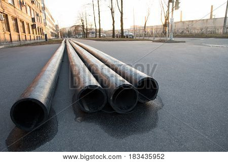 A lot of communication pipes on the pavement in the city located on the left side of the frame shot from a low point