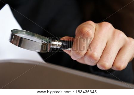 The hand of a man holding a magnifying glass to have himself a closer look.