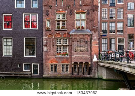 View of typical brick aged residential building and small bridge with bicycles in Amsterdam, Netherlands.