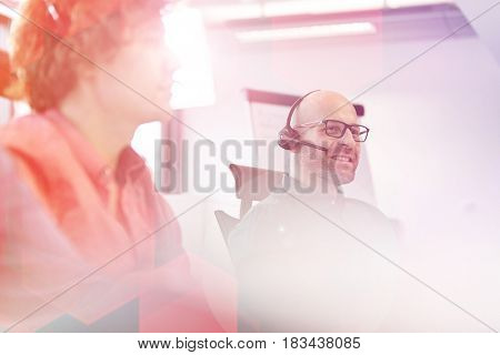 Mid adult businessman using headset with male colleagues in foreground at office