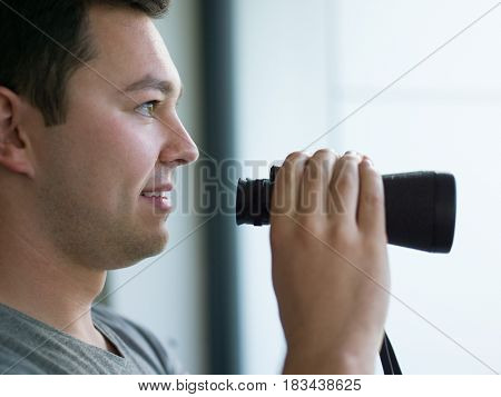 Young man standing looking through a glass window with binoculars as he watches something in the distance