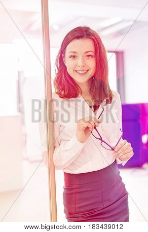 Portrait of beautiful young businesswoman holding eyeglasses in office