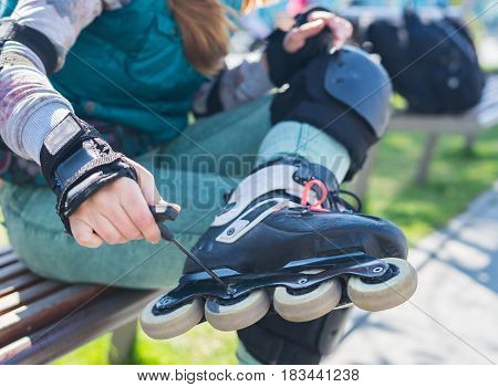 Roller girl unscrewing wheels on freeskate roller Skates with Allen key or Hex key tool. Maintenance of professional skates