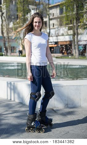 Beautiful and happy Roller Girl skating in the park. She is smiling
