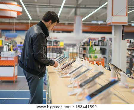 young male customer choosing smartphone in the mobile phone shop. difficult decision
