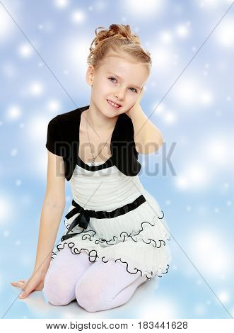 Beautiful little blonde girl dressed in a white short dress with black sleeves and a black belt.Girl straightens hair.