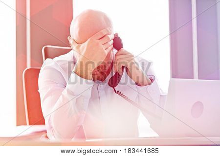 Tired mid adult businessman using landline phone at desk in office