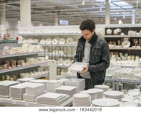 male customer choosing dishes tableware in the supermarket store