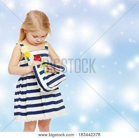 The little blonde girl in a summer striped dress. A girl holds a beach bag.Blue Christmas festive background with white snowflakes.