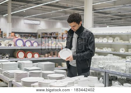 male customer choosing dinnerware plates in the supermarket mall