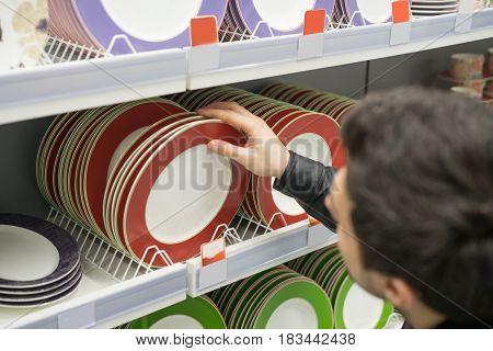 male customer choosing crockery plates in the supermarket mall