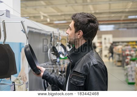 young male customer choosing frying pan in the hypermarket shop