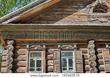 Log hut facade, fragment. Closeup.  Woodcarving. Russian village. Old wooden houses - monument of ancient Russian architecture. Golden ring of Russia, Kostroma