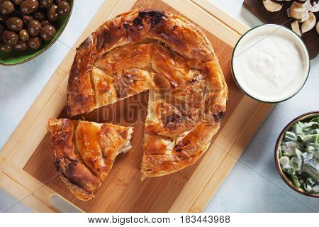 Phyllo pastry cheese pie served with yogurt, salad and olives