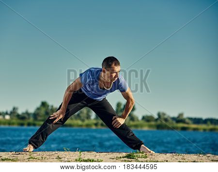 Young healthy active man practicing yoga outdoors