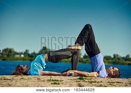 Young healthy man and woman doing acro yoga