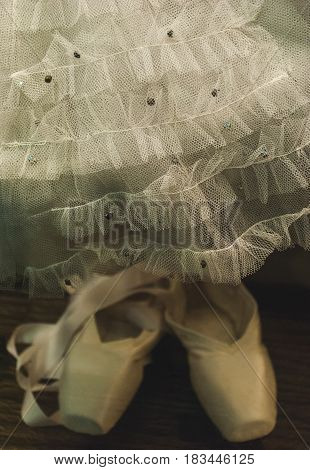 white ballet tutu tulle for a child with sequin paillette and ballet pointe shoes with lace ribbon childhood dreams concept