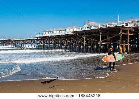 SAN DIEGO, CALIFORNIA - APRIL 21, 2017:  Surfer on Pacific Beach carrying a surfboard near the historic Crystal Pier, the only pier on the California coast with hotel accommodations on the pier.