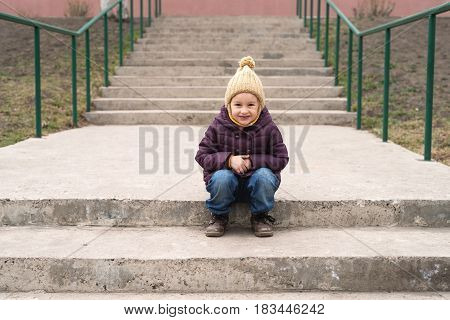 Little girl in a violet coat and a beige woolen hat sitting on the stairs and smilling.