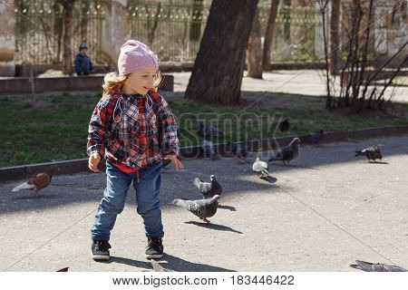 Little girl walks in the park. She is trying to catch pigeons. Spring mood. Outdoors.