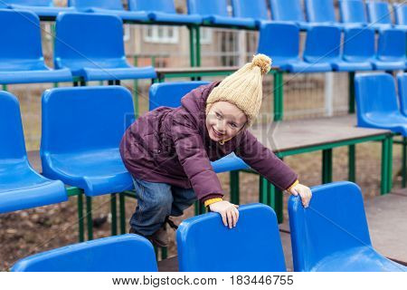 Little girl in a violet coat and a beige woolen hat sitting in a blue seat on a stand.