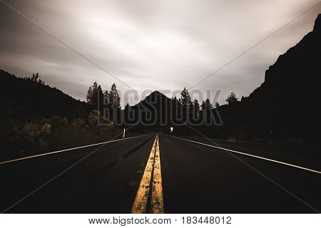 Highway lines leading to silhouette of mountains and trees with cloudy sky above.