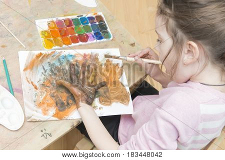 Girl Draws Paints The Picture On Paper And On Hands