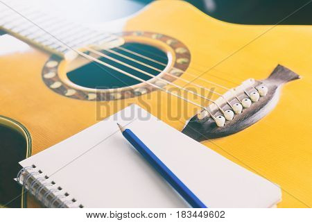 Blank notebook with pencil and guitar for songwriting