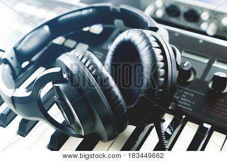 Studio headphone lying on keyboard synthesizer studio