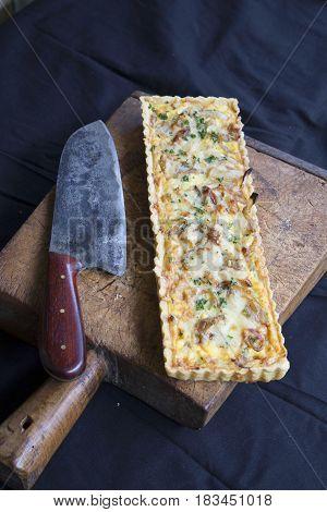 Alsatian Onion Tart With Knife On Wooden Cutting Board