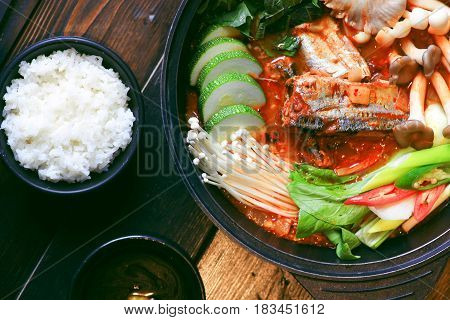 Prepared Hot Pot Of Makerel Fish With Mushroom, Cabbage, Cucumber And White Rice On Table