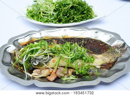 Sauteed Grouper Fish With Soyal Sauce, Onion And Vegetables On Iron Platter