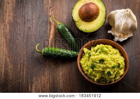 Guacamole with ingredients on wooden table