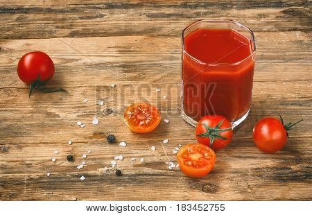 glass of tomato juice cherry tomatoes salt and pepper on an old wooden table