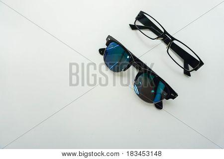 isolated sunglasses and modern men glasses on office desk