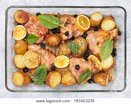 Top view of chicken thighs with potatoes, lemon and black olives, cooked in oven on gray concrete background. Baked chicken leg quarter in heat-proof glass.