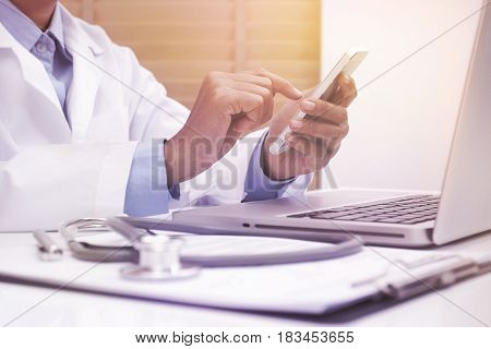 Woman doctor using mobile smart phone and laptop computer at office desk
