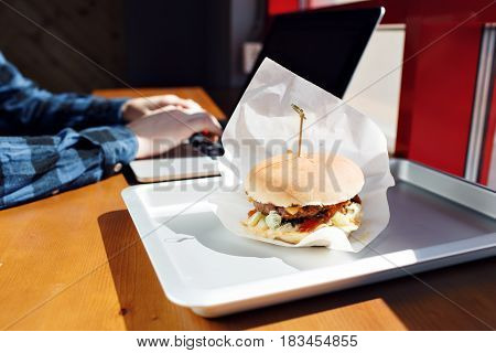 Eating at work place - fast food. burger near laptop. lunch break while you work or sharing online.