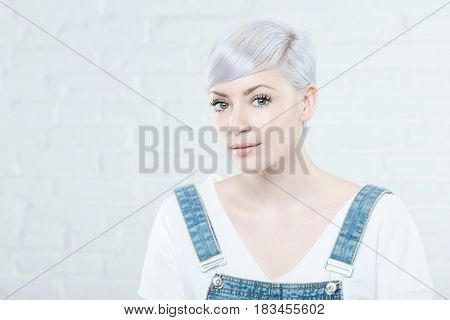 Portrait of platinum blonde young woman looking at camera.