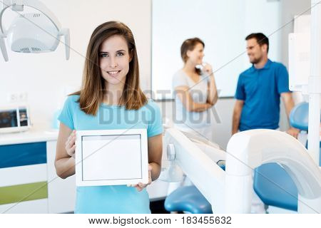 Attractive young dental assistant holding tablet with blank screen.
