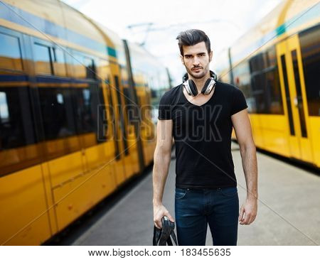 Young man standing at trolley station, between trolleys.