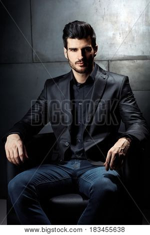 Handsome young businessman sitting in armchair, looking at camera.